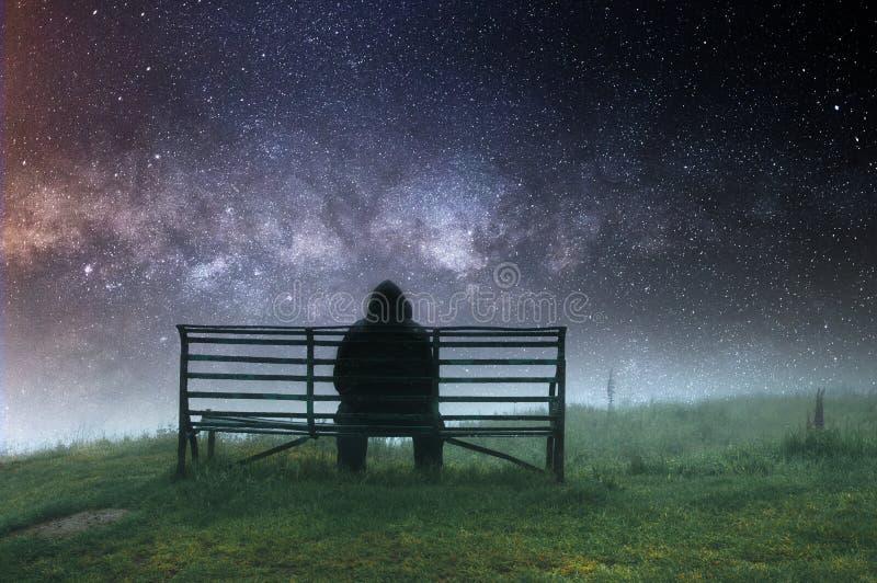 Un homme à capuchon solitaire s'asseyant sur un banc sous la pluie de Th, avec un triste, assourdi, isolée éditent photo libre de droits