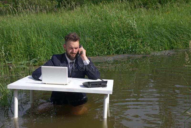 Un homme à une table avec un ordinateur portable écoute soigneusement la conversation au téléphone, essayant de se concentrer sur photographie stock