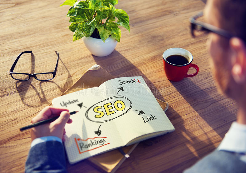 Un homme écrivant SEO Concepts sur sa note photos stock