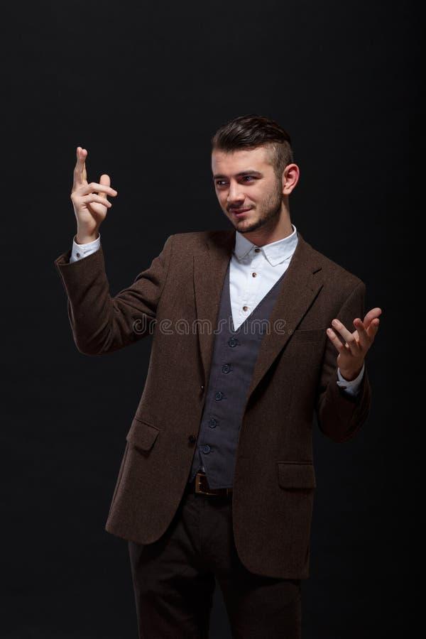Un homme élégant montre quelque chose sur ses mains sur un fond noir photos stock