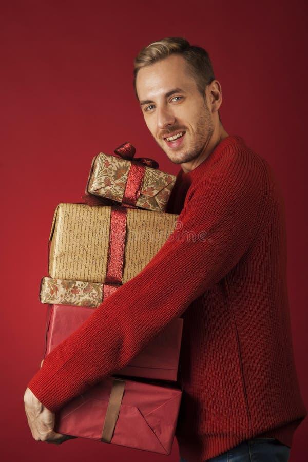 Un homme étreint une boîte de cadeaux de Noël images stock
