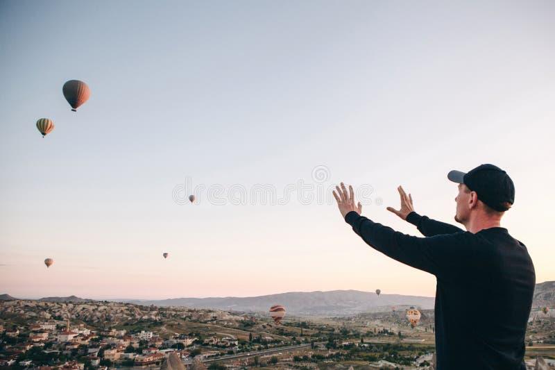 Un homme admire une belle vue des ballons volants images stock