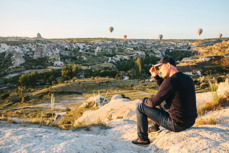 Un homme admire une belle vue des ballons volants photos stock