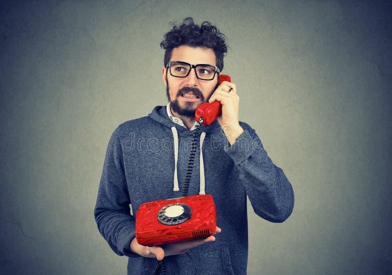 Un homme agacé parlant sur un téléphone démodé photographie stock libre de droits