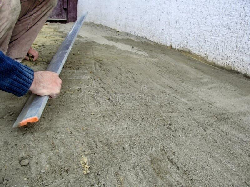 Un homme aplatit la surface d'un mélange de ciment et de sable avec un outil de bordure en plumes de plâtre en aluminium Préparat photographie stock libre de droits