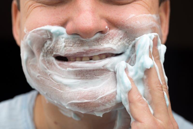 Un homme applique le visage rasant la mousse photos stock