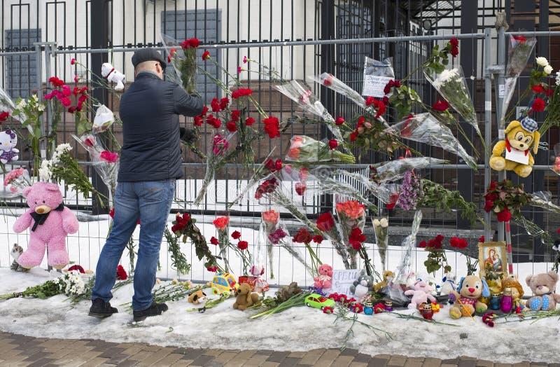 Un homme a apporté des fleurs à l'ambassade de la Russie dans Kyiv photo stock