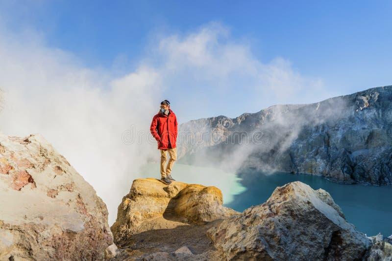 Un homme asiatique utilisant un masque de gaz pour la sécurité sur le volcan de Kawah Ijen avec le lac d'eau sulfurique de turquo photos libres de droits