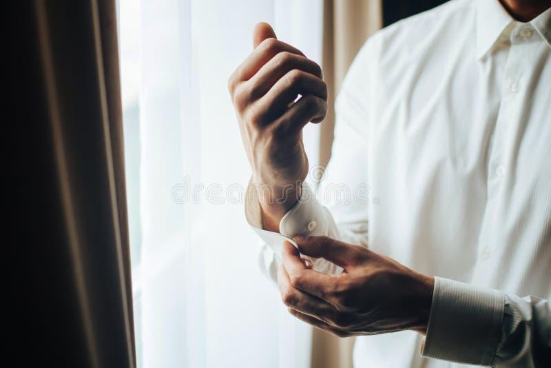 Un homme attache avec un bouton de manchette sur la manchette de la douille d'une chemise blanche luxueuse Fermez-vous d'une main photo libre de droits
