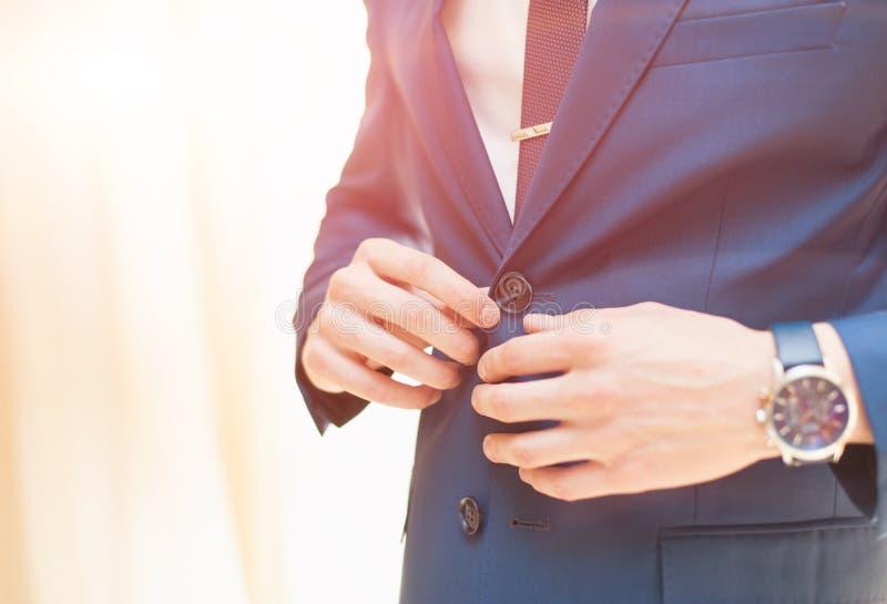 Un homme attache la veste photos stock