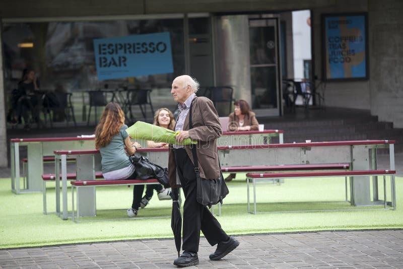 Un homme aux cheveux gris plus âgé dans un costume avec un bouquet des fleurs marche après un café de rue images libres de droits