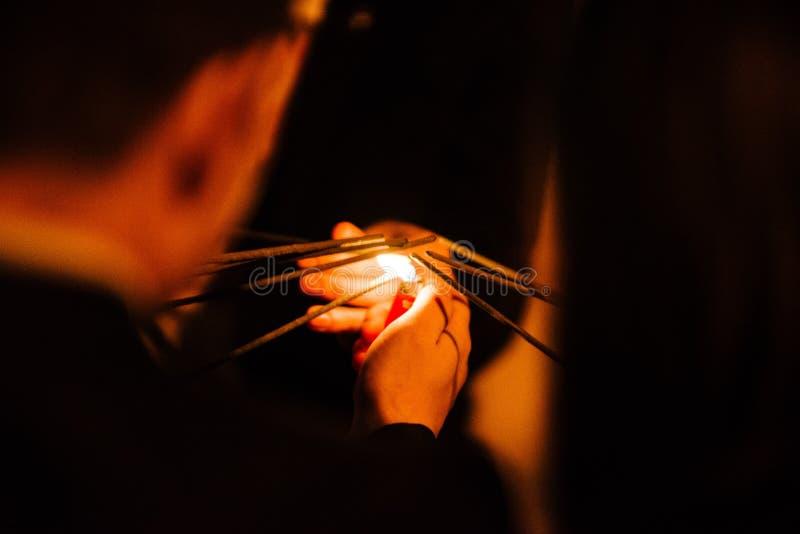 Un homme avec un allumeur de cigarette met les feux sur des cierges magiques la nuit photos libres de droits