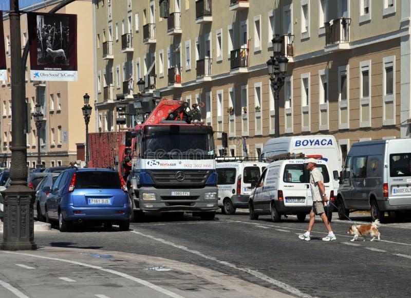 Un homme avec un chien traversant la route sur une rue occupée de ville images stock
