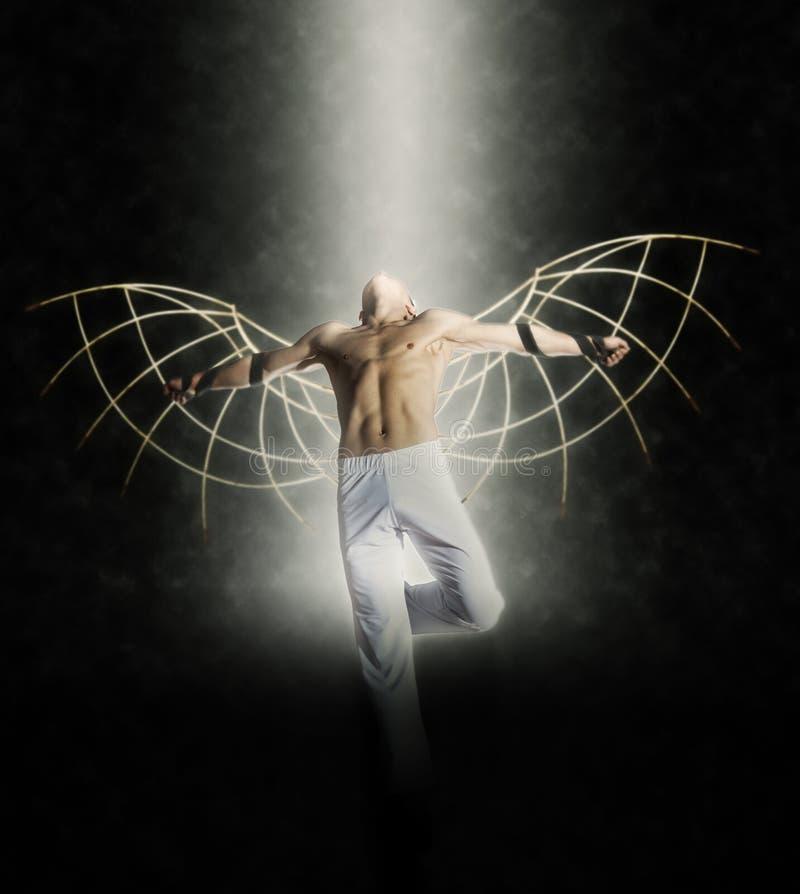 Un homme avec des ailes sur un fond de ciel foncé photos libres de droits