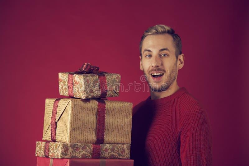 Un homme avec des cadeaux de Noël heureux image stock