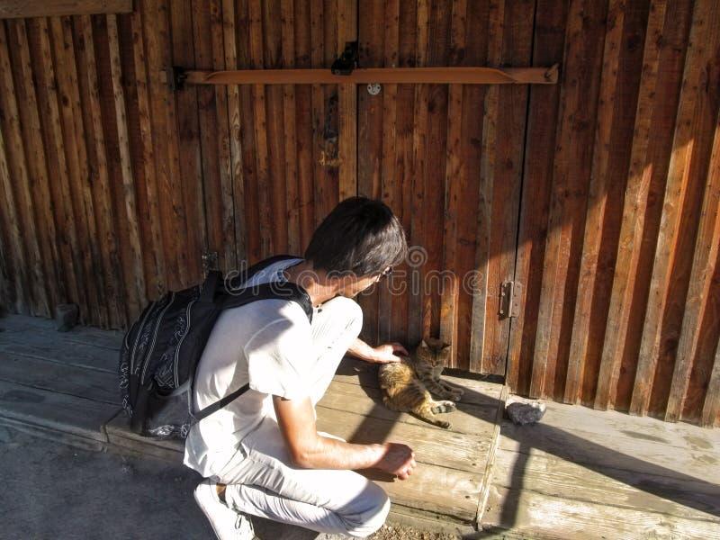 Un homme avec des cheveux foncés et un sac à dos caresse un chat brun près d'un mur en bois images libres de droits