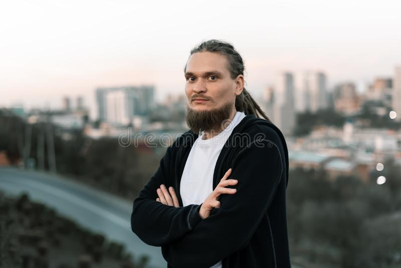 Un homme avec des dreadlocks et une barbe ont croisé ses bras contre la ville image stock