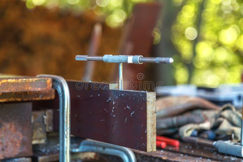 Un homme avec des gants protecteurs sur les mains coupe un fil en métal pour une connexion future photographie stock libre de droits