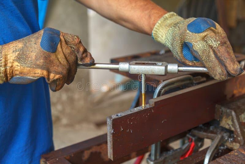 Un homme avec des gants protecteurs sur les mains coupe un fil en métal pour une connexion future photo libre de droits