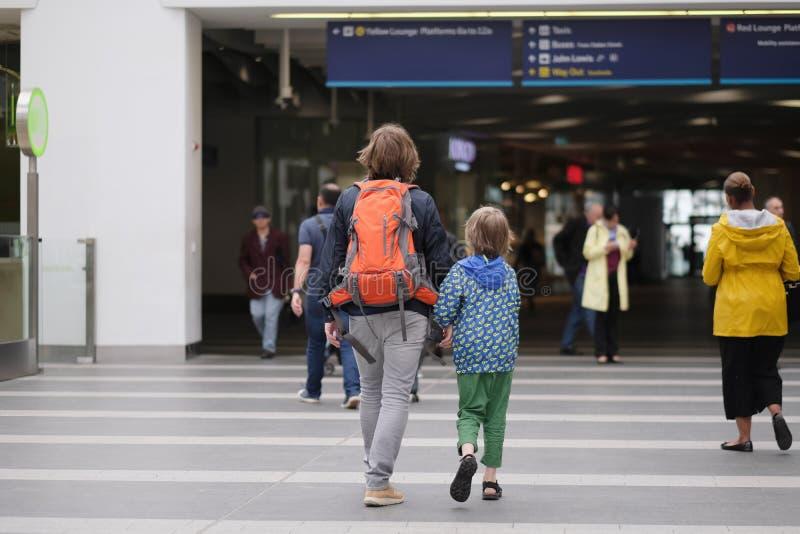 Un homme avec un enfant va à la gare ferroviaire images stock