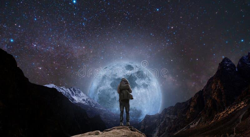 Un homme avec le sac à dos se tenant sur la crête de montagne la nuit, et montagne de silhouette avec la pleine lune et le ciel l photos libres de droits
