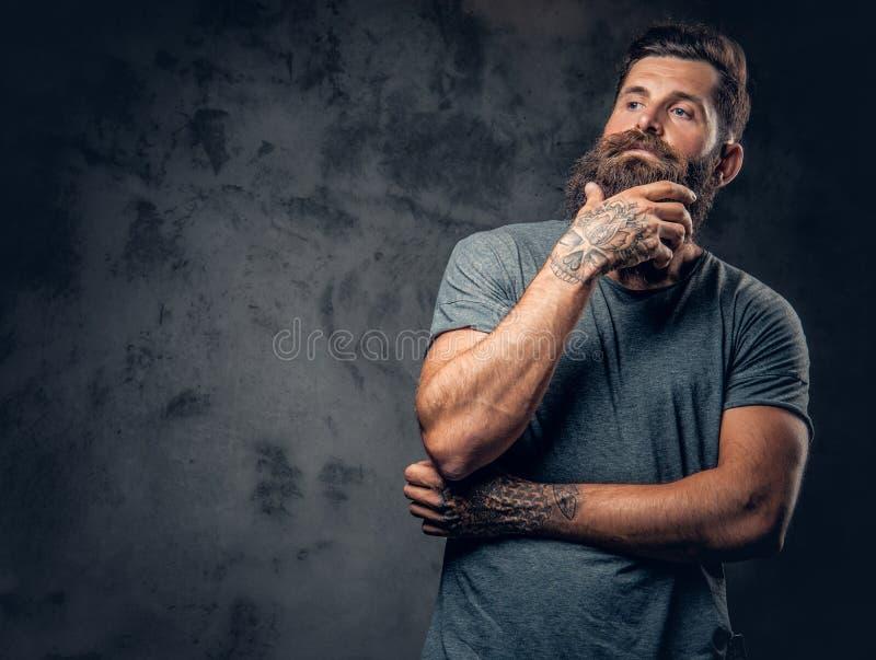 Un homme avec les bras tatoués au-dessus du fond gris-foncé images stock