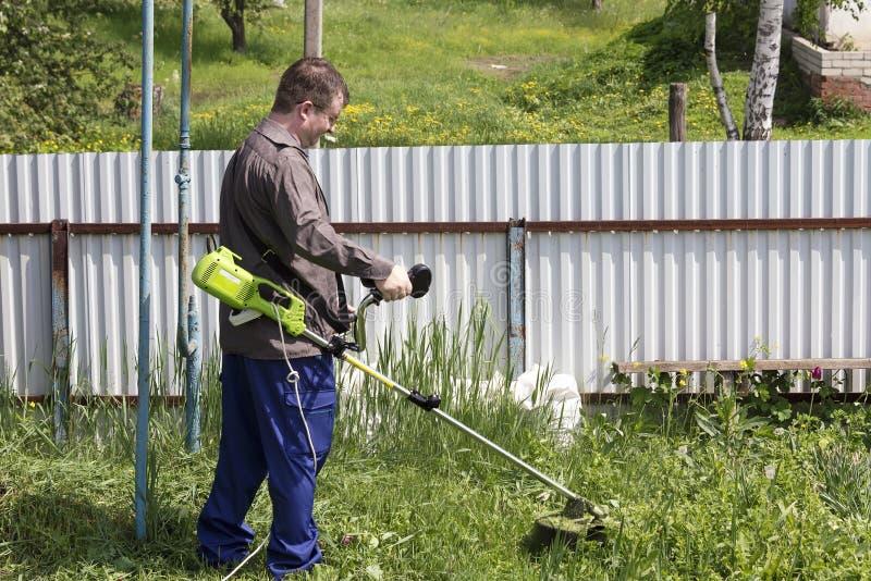 Un homme avec un trimmer fauche l'herbe dans la cour image stock