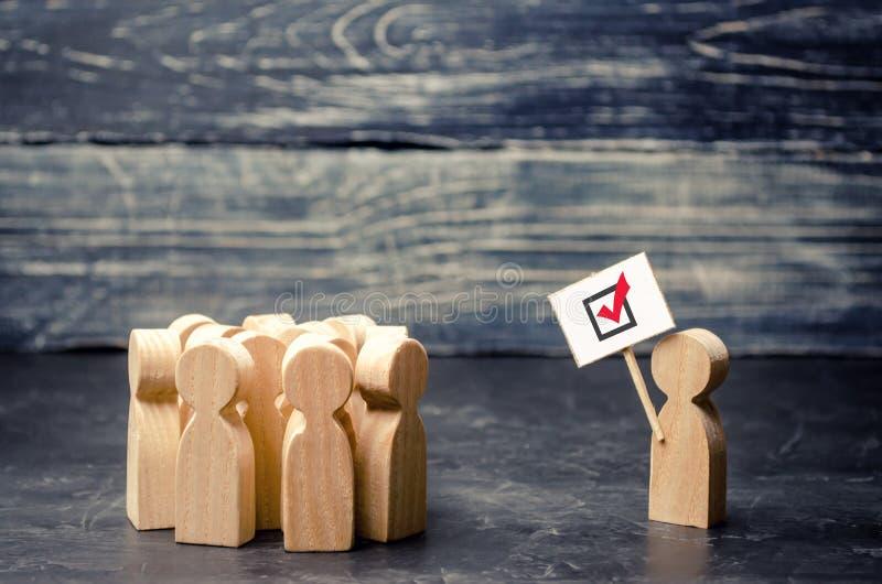Un homme avec une affiche agite un groupe de personnes Électeurs, le processus politique Mouvement politique, faction, partie agi images stock