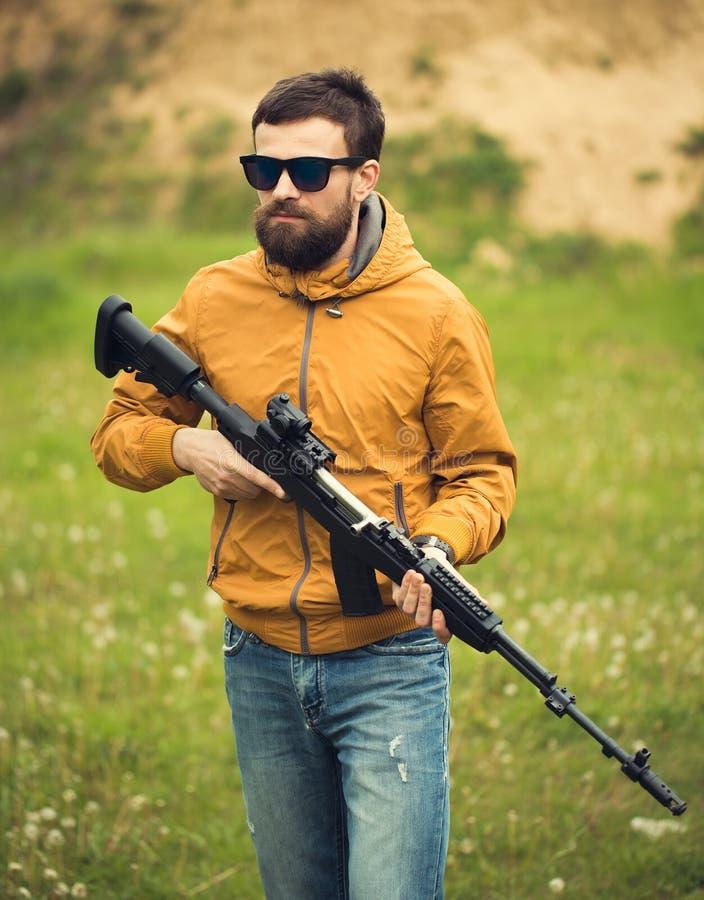 Un homme avec une arme automatique photographie stock