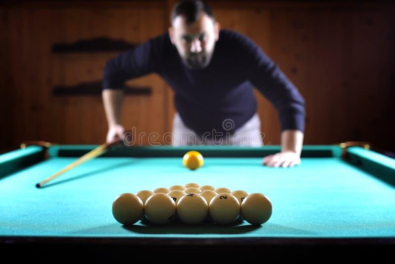 Un homme avec une barbe joue un grand billard Partie dans une piscine de 12 pieds photos libres de droits