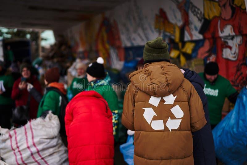 Un homme avec une réutilisation se connectent une veste sur le fond des personnes rassemblant des déchets photographie stock libre de droits