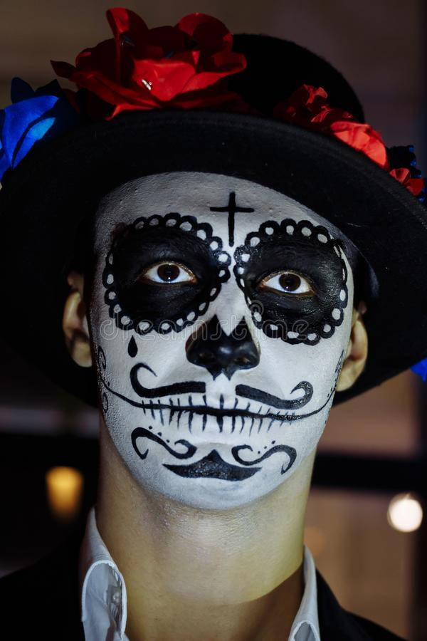 Un homme avec un visage peint d'un squelette, un zombi mort, dans la ville au cours de la journée jour de toutes les âmes, jour d images stock