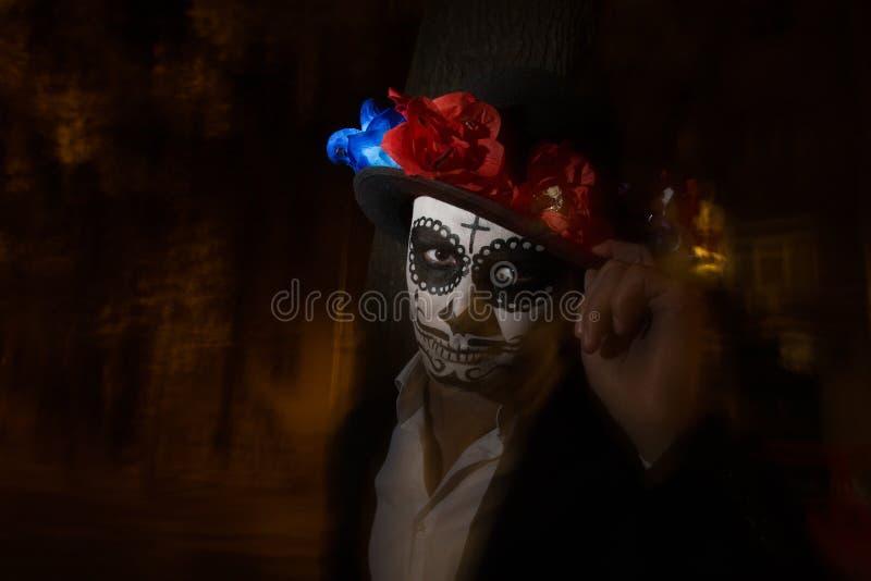 Un homme avec un visage peint d'un squelette, un zombi mort, dans la ville au cours de la journée jour de toutes les âmes, jour d images libres de droits