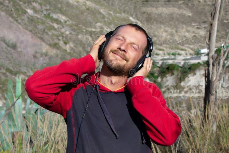 Un homme barbu écoute la musique sur des écouteurs, en nature Il y a des montagnes derrière lui Il est heureux images libres de droits