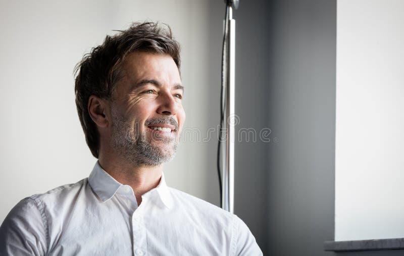 Un homme barbu d'une cinquantaine d'années de sourire regardant la fenêtre l'hôtel photos stock