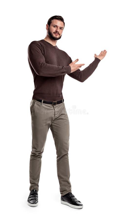 Un homme barbu dans des vêtements sport fait une étape courte et présente quelque chose qui indique avec ses les deux bras photos libres de droits