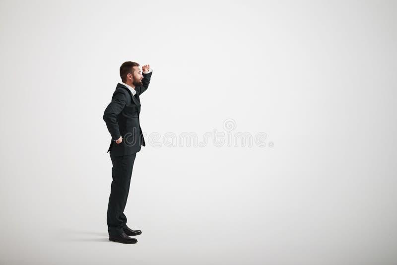 Un homme barbu dans un costume noir examine la distance images stock