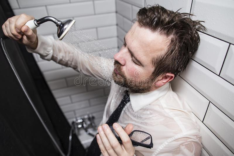 Un homme barbu fatigué dans une chemise et un lien d'affaires a fermé ses yeux photographie stock
