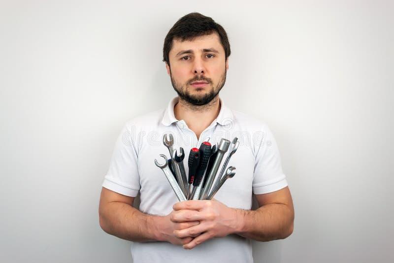 Un homme barbu sérieux d'homme dans un T-shirt blanc avec un bouquet des clés et des tournevis photographie stock