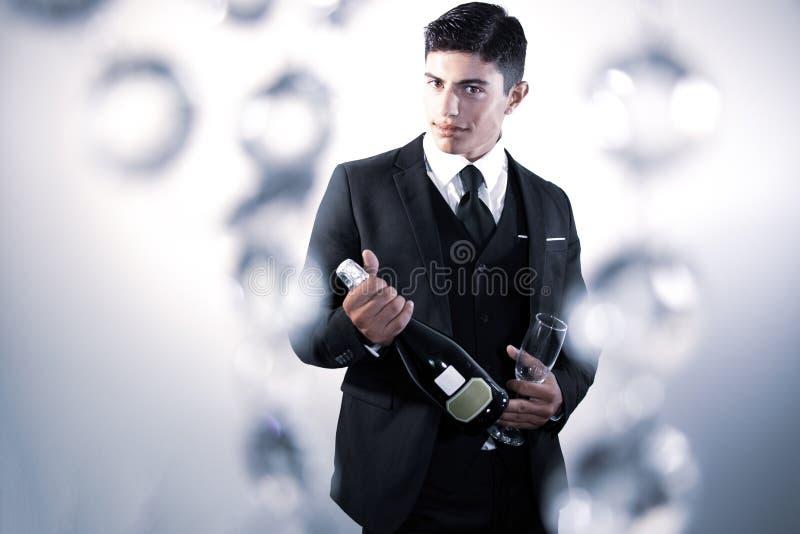 Un homme beau en costume tenant une bouteille de vin mousseux et un verre photographie stock libre de droits