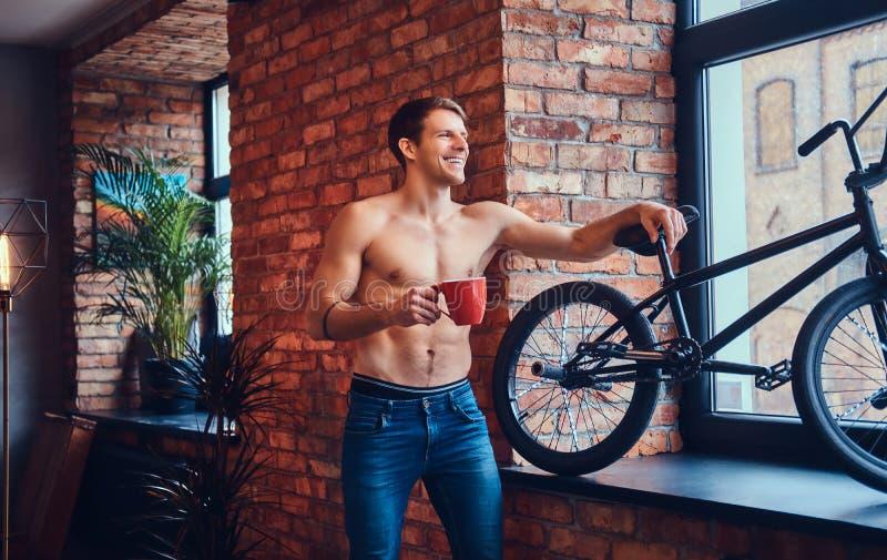 Un homme bel avec BMX dans un studio images stock