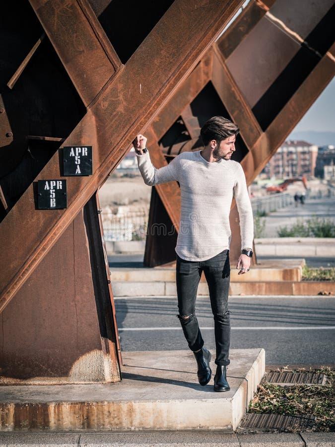 Un homme bel dans la ville fixant la construction métallique rouillée se tenante prêt image libre de droits