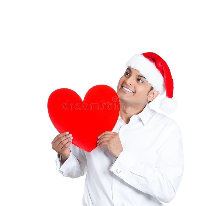 Un homme bel dans le chapeau de Santa a perdu dans des pensées romantiques images libres de droits