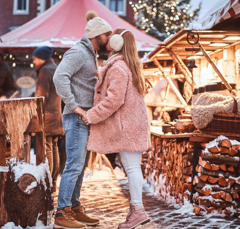 Un homme bel et sa belle amie tenant des mains et les embrassant, appréciant passant le temps ensemble, se tenant au photographie stock libre de droits