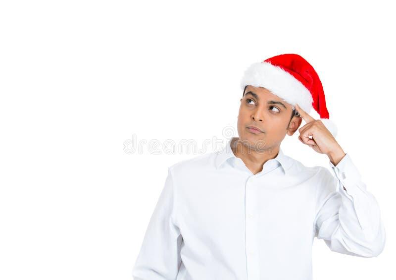 Un homme bel le chapeau rouge de Noël préoccupé et en se demandant images libres de droits