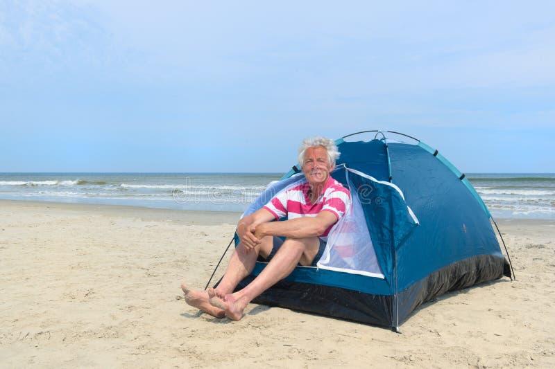 Un homme campant dans un abri à la plage photographie stock libre de droits