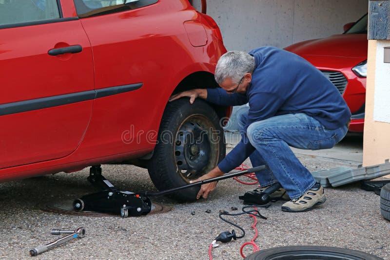 Un homme change des pneus sur une voiture image stock
