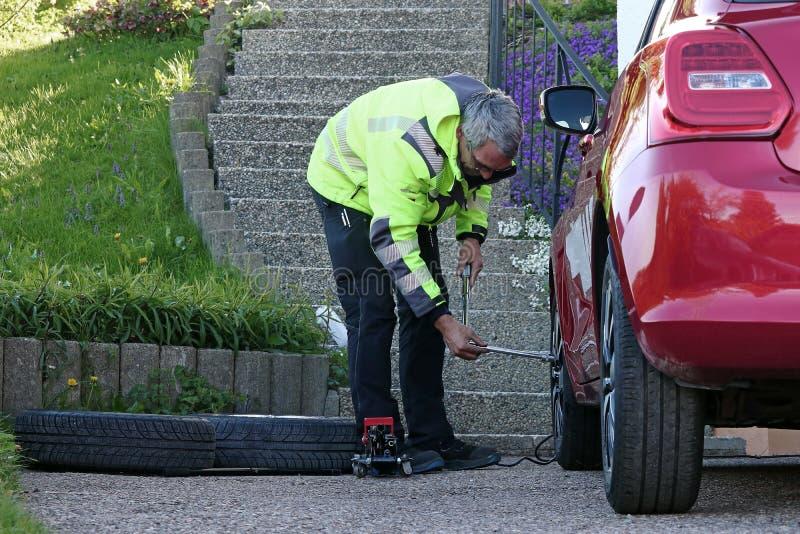 Un homme change les pneus sur sa voiture photo libre de droits