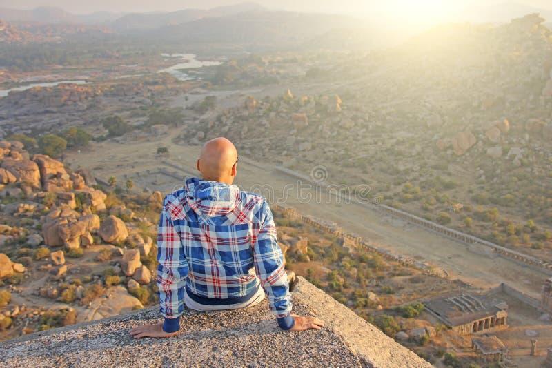 Un homme chauve bel en verres s'assied avec son dos sur un coucher du soleil ou photo libre de droits