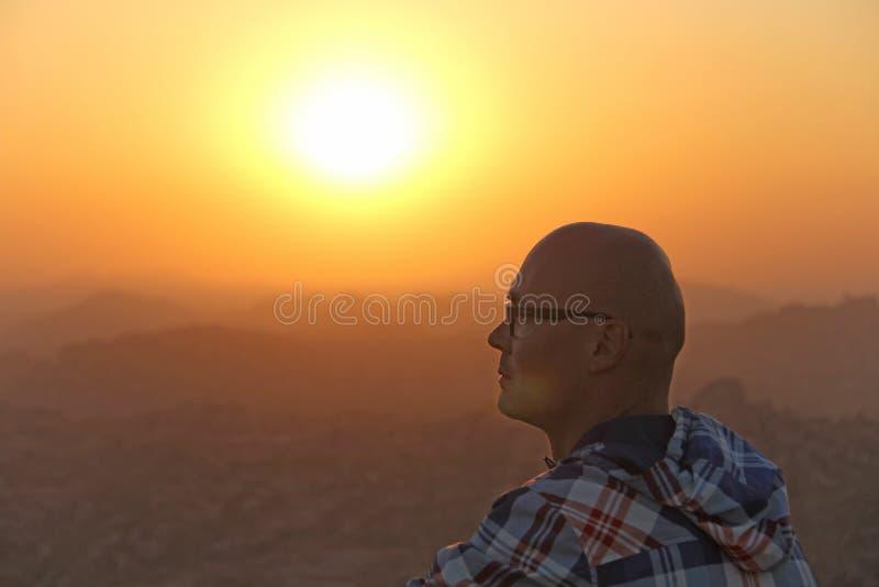 Un homme chauve bel en verres s'assied sur un backgrou de coucher du soleil ou d'aube images stock